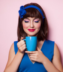 Funny girl with blue cup on pink background