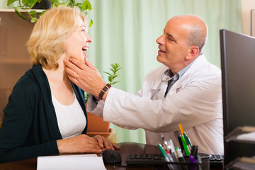 Doctor checking thyroid of  woman