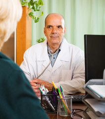 Mature  doctor listening with  female patient