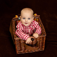 Cute baby boy sitting in a wooden basket
