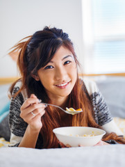 happy asian teen girl eating bowl of chicken noodle soup in bed