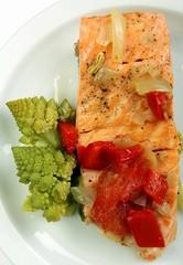 steamed salmon, green cauliflower on a white plate