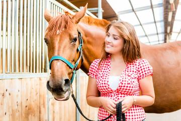 Frau führt Pony in Pferdestall