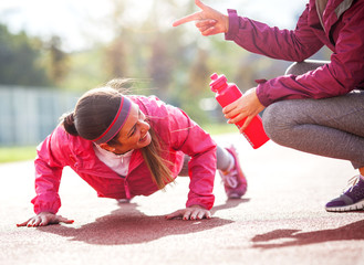 Two attractive female exercising  outdoor.Doing push-ups.