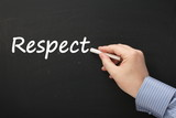 Hand writing the word Respect on a blackboard poster