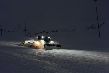 Snowcat cleaning slope in night at snow resort of Gudauri, Georg