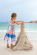 Little girl with sand castle on the beach.