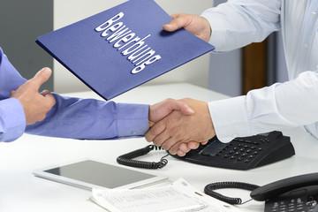 Übergabe Bewerbung mit Handschlag