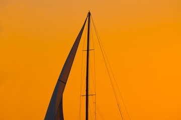 close up of a sail silhouette under an orange sky at sunset