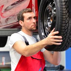 Reifencheck durch Mechaniker in einer Autowerkstatt