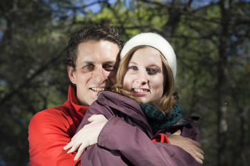 Hombre con chaqueta roja abrazando a su novia por detrás
