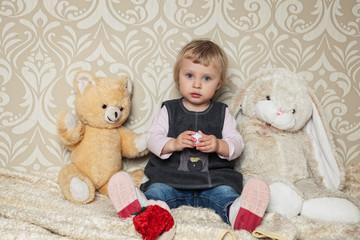 Kind sitzt mit besten Freunden im Zimmer