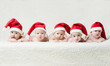 babies with santa hats on bright background - 72571916