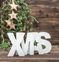 XMAS letter and christmas ornaments over wooden background