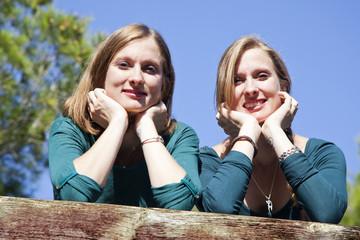 Hermanas gemelas apoyadas sobre barandilla de madera