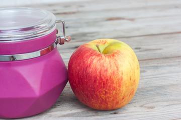 Apple and purple jar on the wooden floor.
