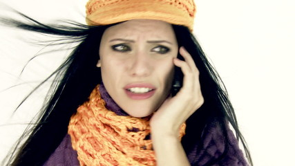Woman talking on the phone worried with hat scarf and wind