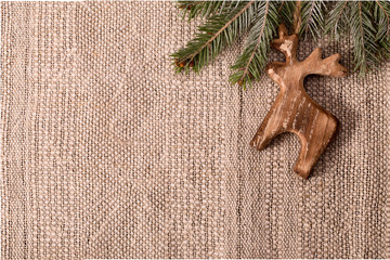 Christmas decoration with fir branch and wooden deer at top righ