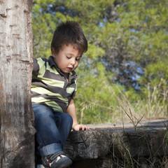 Niño sentado en puente de madera