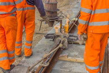 Workers in orange welding tracks