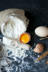 flour  in burlap with wooden spoon and eggs  on a gray cloth