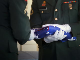 Guard Folds United States Flag at Veteran Funeral