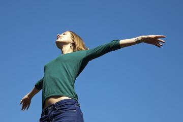 Chica rubia con jersey verde abriendo los brazos al cielo