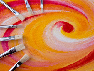 Painting brushes on a colorful canvas
