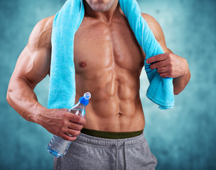 Fitness Athletic Man holding bottle of water and towel