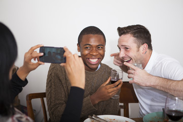 Three friends having healthy dinner and taking photos