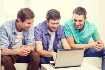 smiling friends with laptop computer at home