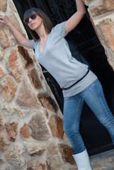 Charming teen in casual posing against black door