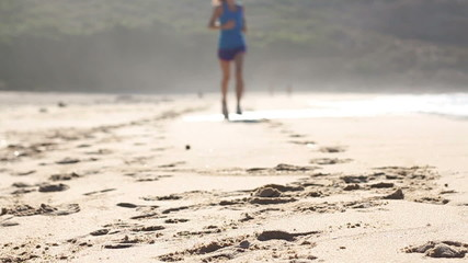 Feet of young woman jogging on the beach, slow motion