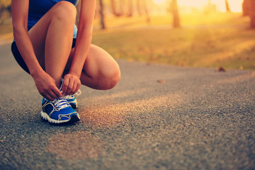 woman runner tying shoelace on trail