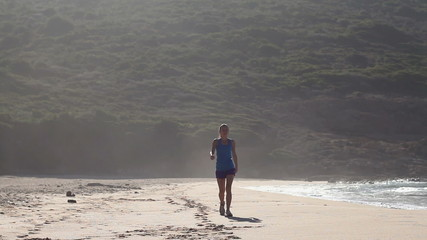 Athletic young woman walking on the beach