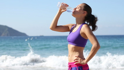Woman drinking water after jogging, slow motion