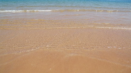 shallow of sea on gold sand beach
