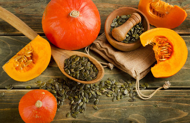 Orange pumpkins and seeds  on a wooden table.