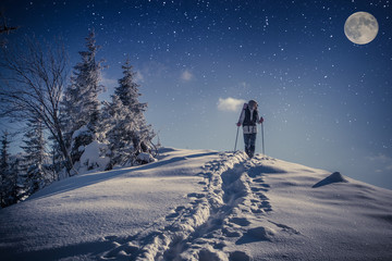 Travel in winter mountains at night with stars and a full moon