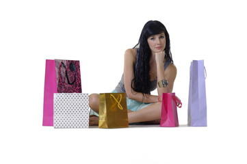 Young attractive shopper girl sitting with purchases
