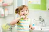 Fototapety kid girl brushing teeth in bathroom