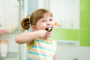 Funny kid girl brushing teeth in bathroom