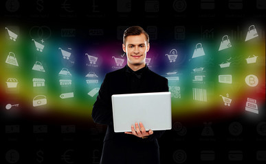 Smiling young man standing with laptop