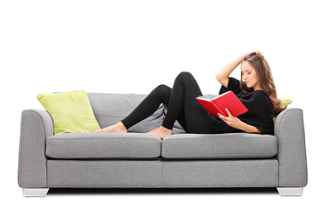 Relaxed young woman reading a book seated on sofa