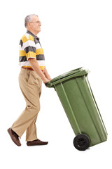 Senior pushing a large green trash can