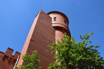 A red- brick tower with some greenery