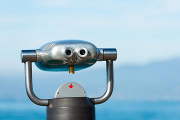 Public Binoculars on a Blue Blurred Landscape