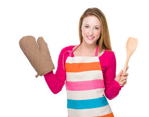 Housewife with oven gloves and wooden spatula