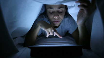 Tired Woman Using Digital Tablet under Bed Sheets