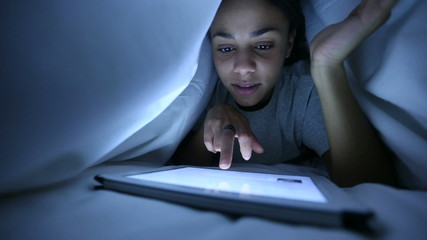 Beautiful Woman Using Digital Tablet under Bed Sheets